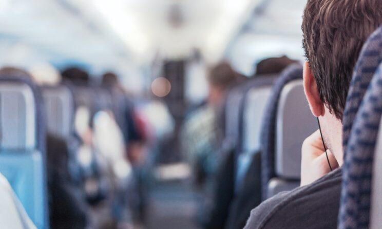mand sidder i fly og kigger igennem midtergangen